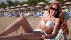 Slim girl with red hair tans on the beach and smiling. Stock Footage