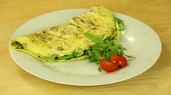 Omelet with herbs and tomatoes rotates on a wooden boards background Stock Footage