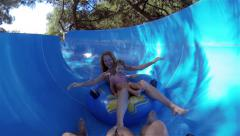Crazy Water Race. Young mother with daughter fun slide down the water slide. Stock Footage