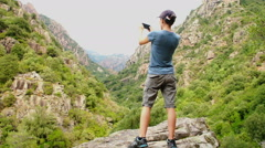 Hiking woman taking photo with smart phone at mountain peak HD Stock Footage