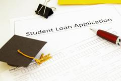 student loan application form and mini graduation cap - stock photo