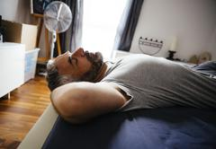 Man sleeping on his bed at daytime - stock photo