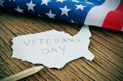 piece of paper in the shape of united states with the text veterans day - stock photo
