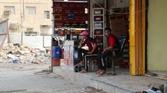 Two Young Men Sitting in Front of Shop Waiting for Customers Stock Footage