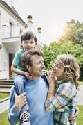 Young family in front of villa - stock photo