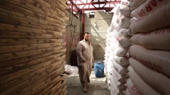 Man Dressed in Islamic Thawb Walks in Narrow Hallway of Grain Sacks Stock Footage