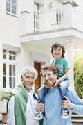 Young family with grandfather in front of villa - stock photo