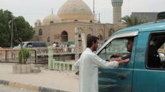 Two Iraqi Men Have Discussion in Foreground of Baghdad Mosque Stock Footage