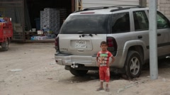 Young Boy Stands with Hands on Hips on Baghdad Street with Hands on Hips Stock Footage