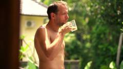 Young man drinking coffee, in towel on terrace HD - stock footage