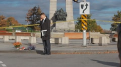 Officer on phone by war memorial Stock Footage
