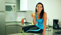 Sporty woman sitting in the kitchen and reading gossip magazine, steadycam shot Stock Footage