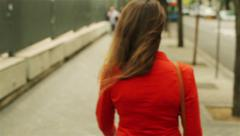 Woman in red jacket walking on the street, steadycam shot Stock Footage