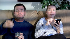 happy male female couple sitting on couch watching TV cell phone people lifes - stock footage