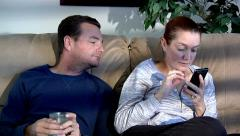male female couple sitting on couch watching TV cell phone people lifestyle r - stock footage