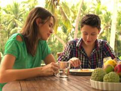 Mother and son talking on terrace and spreading jam on toast  NTSC Stock Footage