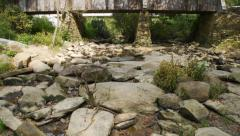 Tilt up from creek bed to covered bridge Stock Footage