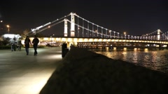 Young Couple Walk in Foreground of Beautifully Lit Bridge Stock Footage