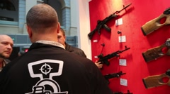 Pan Shot of Rifles and Exhibitor Talking with Customers Stock Footage