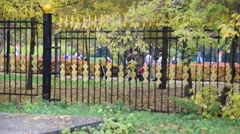 Fall Colors Silhouette Pedestrians Walking Outside Park Gate Stock Footage