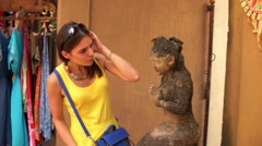 Pretty woman looking and checking ancient sculpture HD Stock Footage