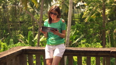 Young, pretty woman using tablet computer on terrace HD Stock Footage