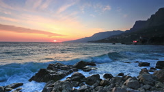 Sea waves with splashes break about stones early in the morning at sunrise Stock Footage