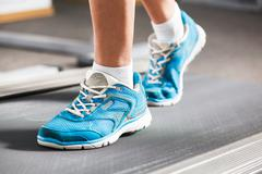 Woman running on treadmill in gym. Stock Photos