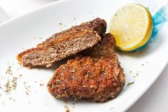 fried veal medallion cut with lemon. - stock photo
