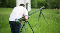 Man installs homemade crane for camera, shooting outdoors Stock Footage