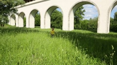 Little boy walks in grass and finds sticks near aqueduct Stock Footage
