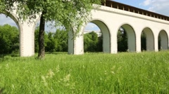 Old aqueduct among grass at sunny day in Moscow, Russia Stock Footage