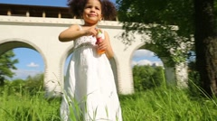 Brother with toy gun and sister stand on grass near aqueduct Stock Footage