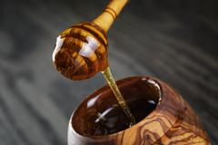 Maple honey flowing from dipper to pot Stock Photos