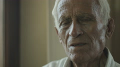 confused and thoughtful old man portrait: mental illness, discomfort, disease - stock footage