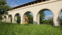 Girl in dress goes and spins on grass near aqueduct at summer Stock Footage