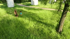 Pretty woman and little girl go on green grass at summer Stock Footage