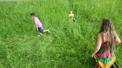 Girl and little boy play catch-up and other boy lies on grass Stock Footage
