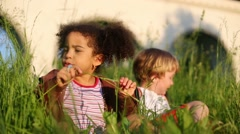 Pretty little girl and boy sit on green grass and girl eat blade Stock Footage