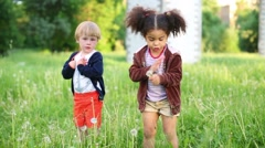 Little girl and boy rip off dandelions on grass at summer day Stock Footage
