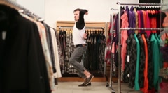 Young handsome man dances in small fashionable clothing store - stock footage