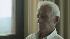 thoughtful old man sitting alone: loneliness, fear, sadness, sad, thoughts - stock footage