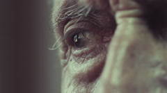 sad man sitting lonely near window: eye close-up, wrinkles and signs of aging - stock footage