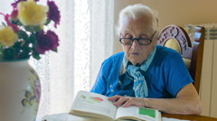 Old woman reading a  book of science - elderly Stock Footage