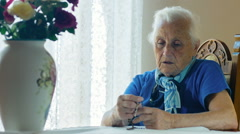 depressed old woman praying with rosary beads: faith, religion, seeking of god - stock footage