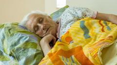 awakening of an elderly woman: loneliness, depression, sadness - stock footage