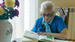 Very old woman reading book sitting at the table in her living room Stock Footage