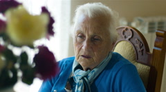 pensive old woman: thoughtful old woman sitting alone, sadness, sad woman - stock footage