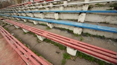 Long dirty destroyed blue and red grandstands at old stadium Stock Footage