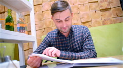 Young, handsome man, sitting in a restaurant chooses a course for dinner Stock Footage